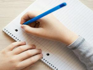 Mão segura caneta azul em folha de caderno