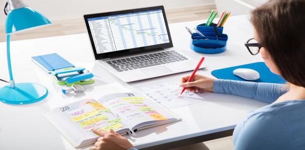 Estudante escreve em agenda em frente a um notebook