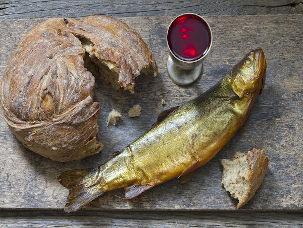Pão, vinho e peixe em cima de mesa de madeira
