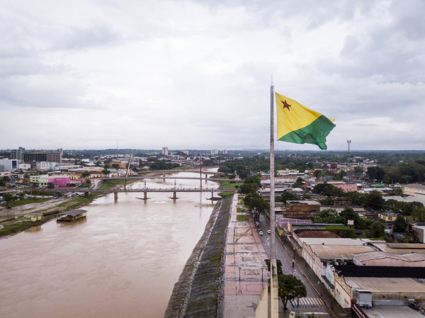 Foto do rio Acre, que divide a capital Rio Branco; à direita, está a bandeira do Acre, nas margens do rio, há construções.