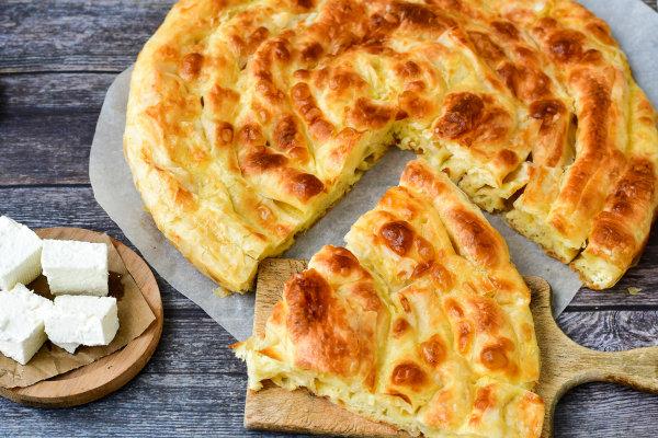 Foto de um banitsa, prato tradicional da Bulgária, fatiado e cubos de queijos sobre tábuas de madeira.
