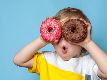 Criança segurando donuts