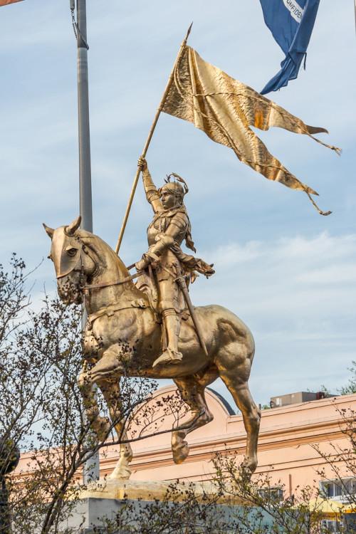 Estátua dourada retratando Joana d'Arc em cima de um cavalo e segurando uma bandeira.