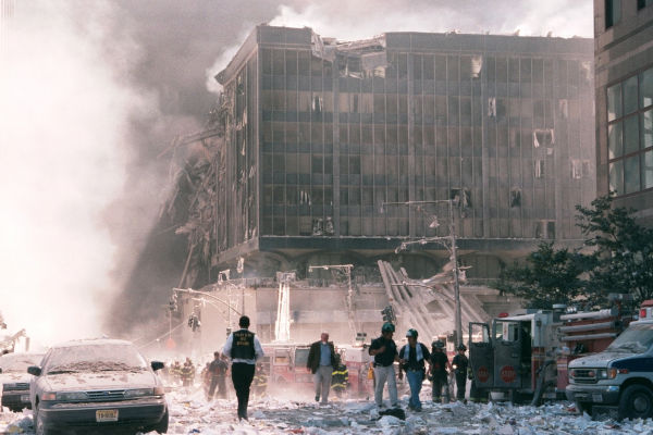 Destroços dos atentados de 11 de setembro e pessoas andando na rua.