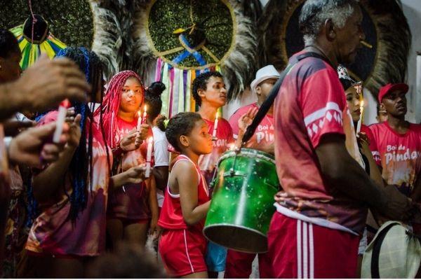 Foto de pessoas celebrando o bumba meu boi no Maranhão, com percussão e velas.
