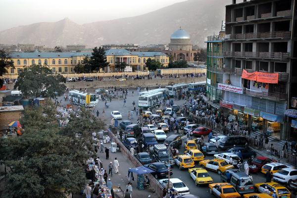 Vista do centro de Cabul mostrando multidão e carros; ao fundo, há uma mesquita e colinas.