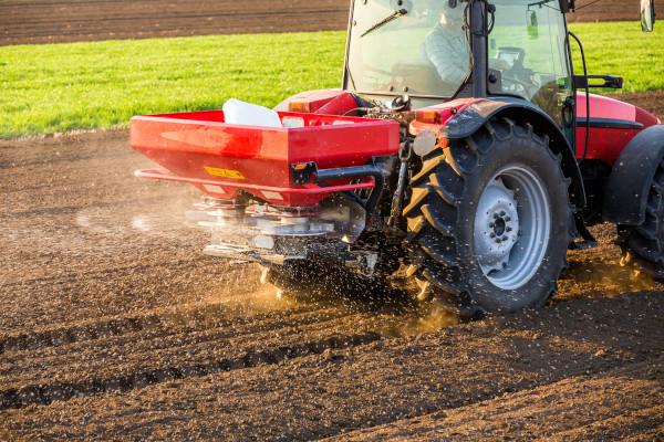 Fazendeiro utilizando terras aráveis com potássio, nitrogênio e fósforo.