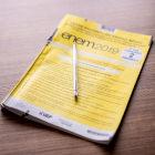 Caderno amarelo do Enem sob mesa de madeira