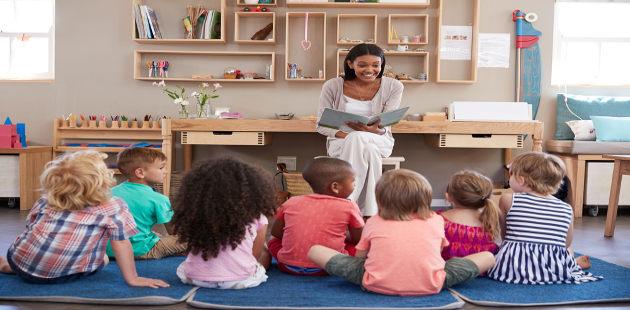 Professora sentada na cadeira e com um livro na mão conta história para alunos sentados no chão