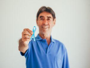 Homem com camisa azul segura laço símbolo do novembro azul