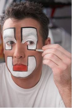 Palhaço passando alvaiade (óxido de zinco) como maquiagem.