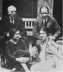 Böhr (à direita), sua esposa à sua frente e ao seu lado Ernest Rutherford (à esquerda)