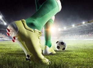 Close de pés com chuteira prestes a chutar a bola em campo de futebol