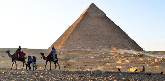 Homens sob camelos e pirâmide ao fundo