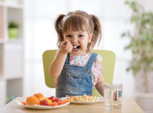 Criança comendo com prato à mesa em sua frente