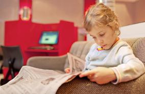 Menina lê jornal