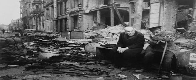 Homens sentados em meio aos destroços da Batalha de Berlim