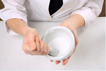 Triturando bicarbonato e açúcar com almofariz e pistilo