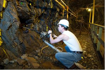 Mineiro em túnel subterrâneo extraindo carvão mineral