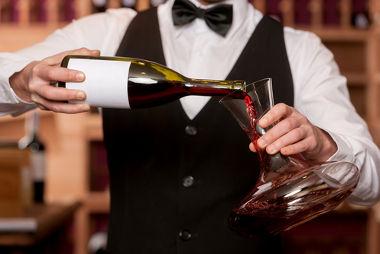Garçom decantando vinho tinto antes de ser servido