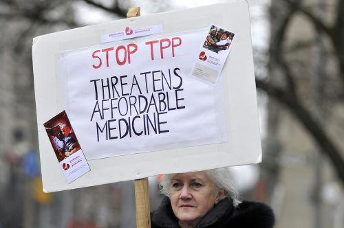 """Manifestante com cartaz contra a aprovação do TPP que diz: """"Pare o TPP, ameaça aos medicamentos acessíveis"""" *"""