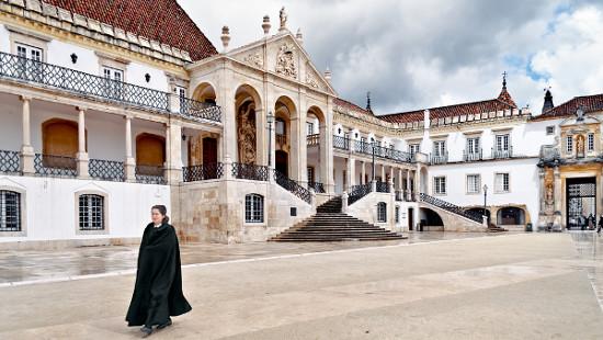 Estudante caminha pela Universidade de Coimbra com seu uniforme