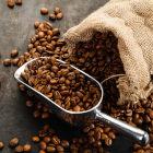 Grãos de café em saco de pano e espalhados sob superfície de madeira