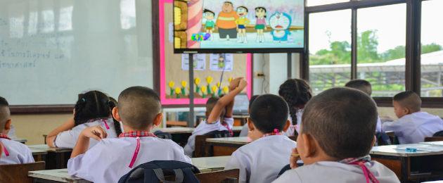 Crianças em sala de aula assistindo TV
