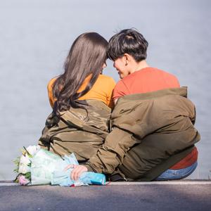 namoradas na beira de lago com buquê de flores