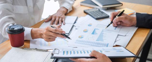 Homem com documentos e caneta na mão fazendo cálculos em calculadora