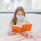 Criança doente com máscara lendo um livro