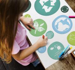 Criança colando símbolos de sustentabilidade em cartolina sob a mesa