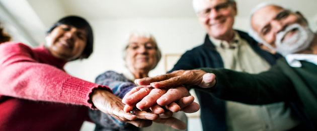 Grupo de idosos colocando as mãos umas sob as outras