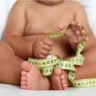Bebê segurando fita métrica